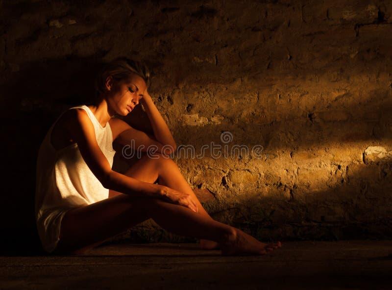 Mujer joven sola que se sienta en la calle imagen de archivo