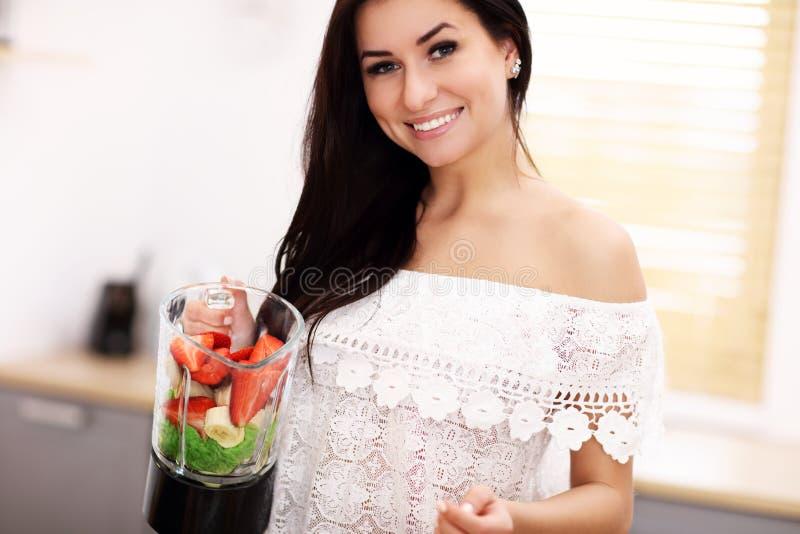 Mujer joven sonriente apta que prepara el smoothie sano en cocina moderna fotografía de archivo