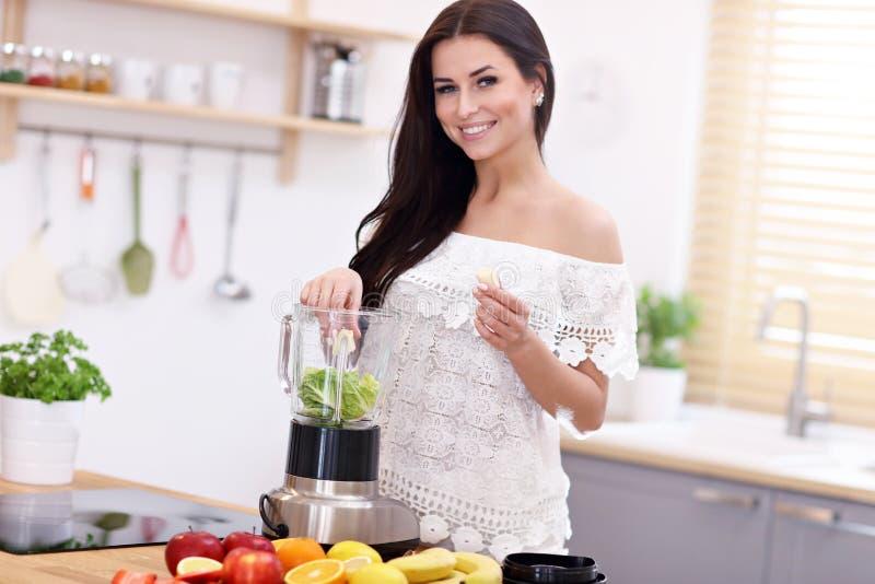 Mujer joven sonriente apta que prepara el smoothie sano en cocina moderna fotografía de archivo libre de regalías