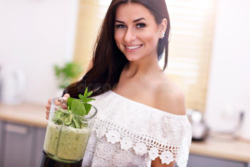 Mujer joven sonriente apta que prepara el smoothie sano en cocina moderna foto de archivo
