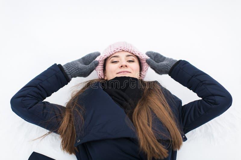Mujer joven sonriente atractiva en nieve en sombrero hecho punto foto de archivo libre de regalías