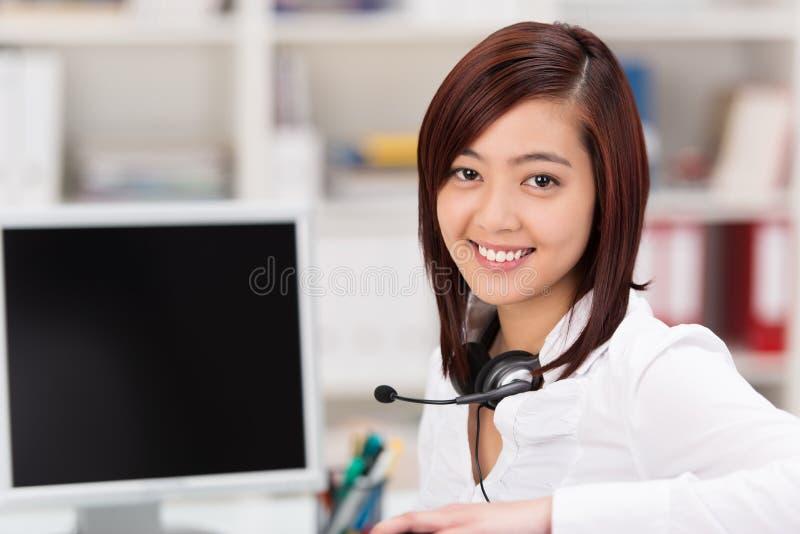 Mujer joven sonriente con auriculares alrededor de su cuello imágenes de archivo libres de regalías