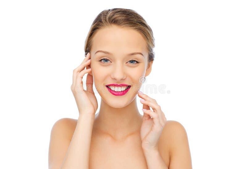 Mujer joven sonriente con el lápiz labial rosado en los labios imagenes de archivo