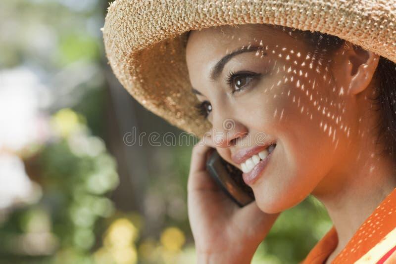 Mujer joven sonriente con el teléfono celular imagenes de archivo