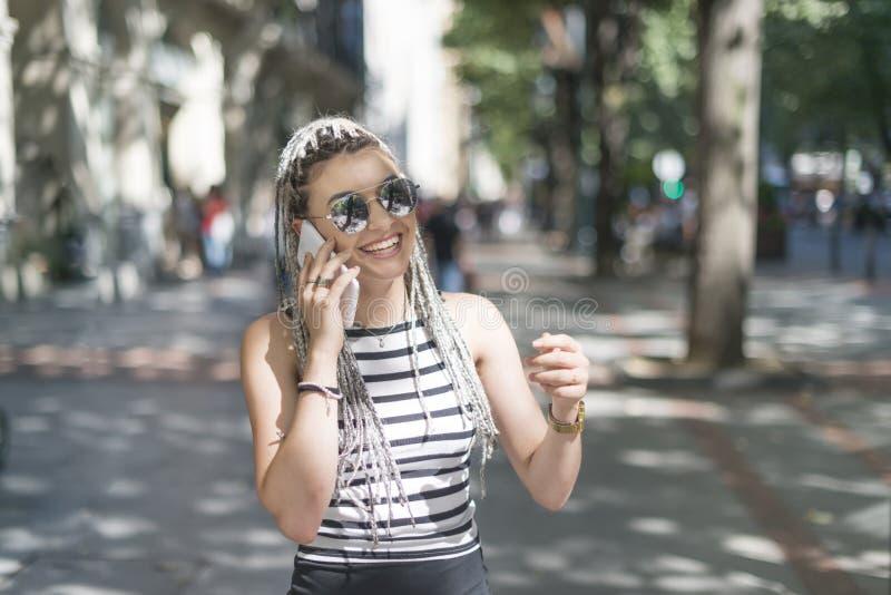 Mujer joven sonriente con el teléfono elegante fotografía de archivo