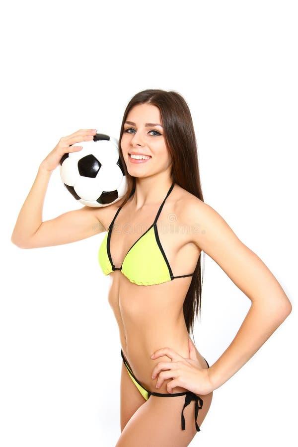 Mujer joven sonriente con el traje de baño que sostiene un balón de fútbol en un whi imágenes de archivo libres de regalías