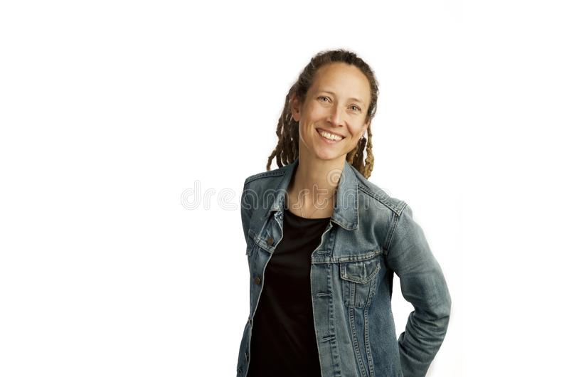 Mujer joven sonriente con la chaqueta del dril de algodón y dreadlocks aislados en el fondo blanco fotos de archivo libres de regalías