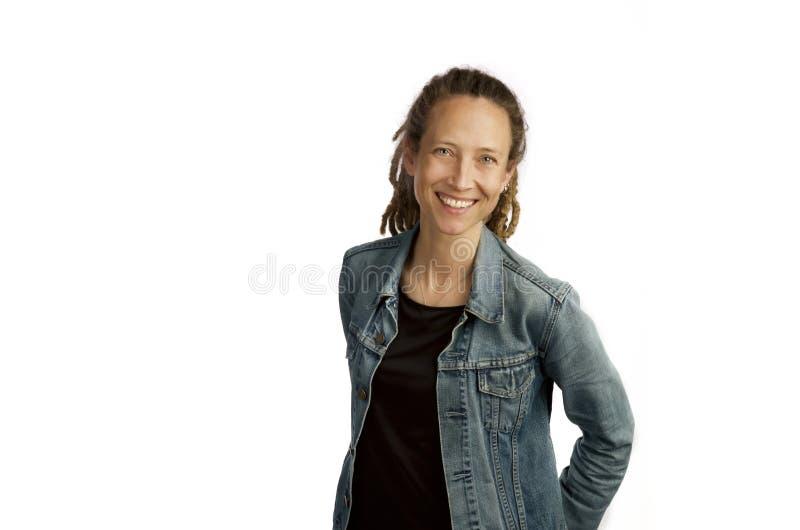 Mujer joven sonriente con la chaqueta del dril de algod?n y dreadlocks aislados en el fondo blanco foto de archivo