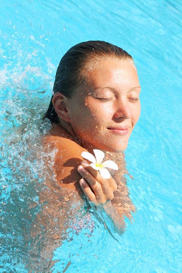 Mujer joven sonriente con la flor en piscina foto de archivo libre de regalías