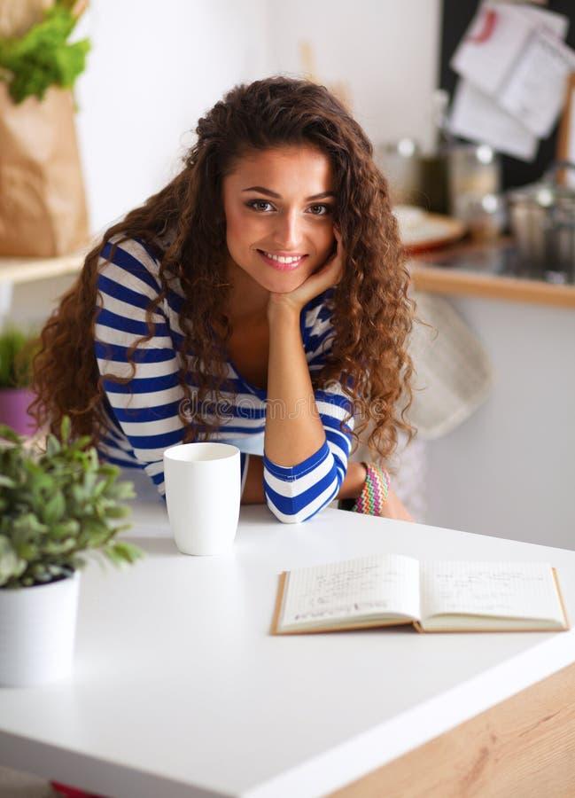 Mujer joven sonriente con la taza de café en la cocina fotografía de archivo libre de regalías