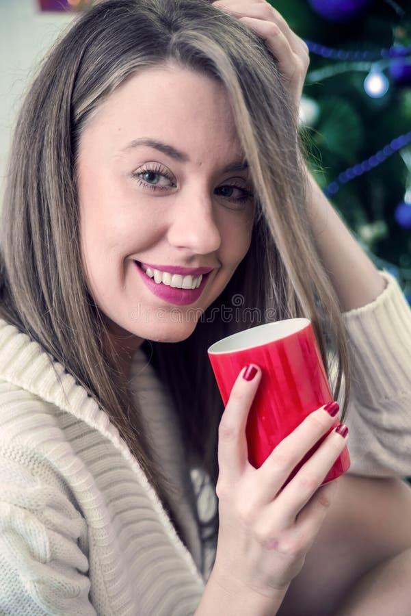 Mujer joven sonriente con la taza de chocolate caliente delante de luces de la Navidad fotos de archivo libres de regalías