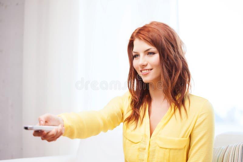Mujer joven sonriente con la TV teledirigida en casa imagen de archivo