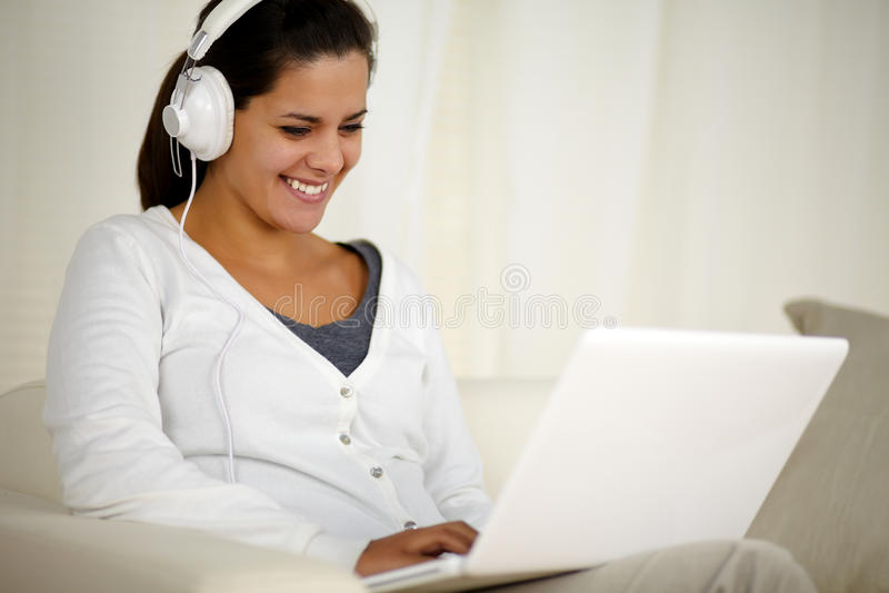 Mujer joven sonriente con música que escucha del auricular foto de archivo libre de regalías