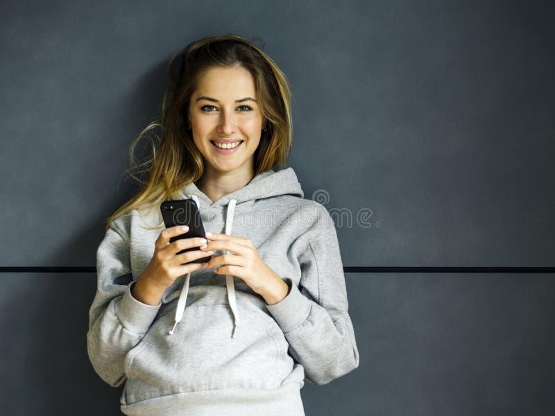 Mujer joven sonriente con su teléfono móvil fotos de archivo libres de regalías