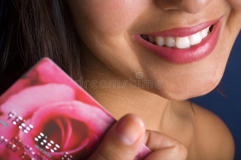 Mujer joven sonriente con un de la tarjeta de crédito fotografía de archivo