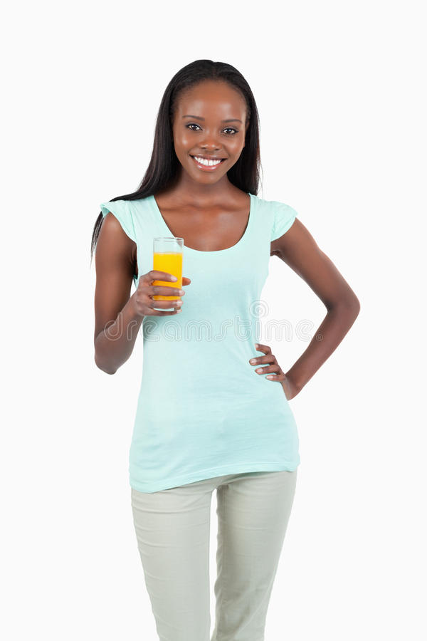 Mujer joven sonriente con un vidrio de zumo de naranja imagen de archivo