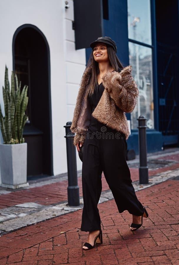 Mujer joven sonriente de la moda que camina en la ciudad imagenes de archivo