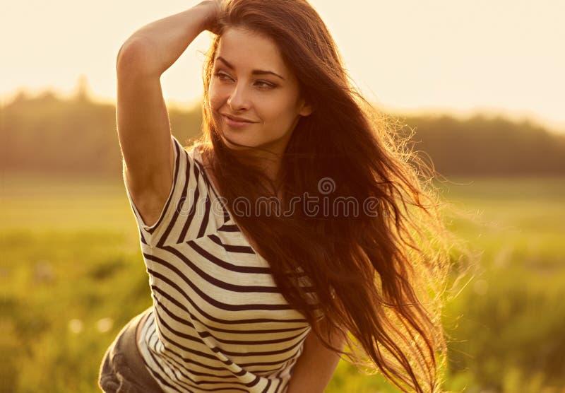 Mujer joven sonriente de pensamiento hermosa que parece feliz con el pelo brillante largo en fondo del verano de la puesta del so foto de archivo libre de regalías