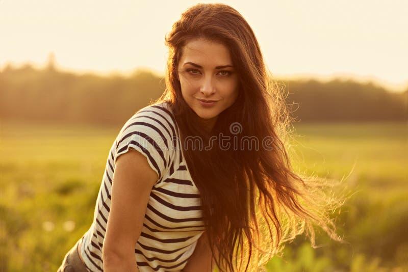 Mujer joven sonriente de pensamiento hermosa que parece feliz con el pelo brillante largo en fondo del verano de la puesta del so foto de archivo