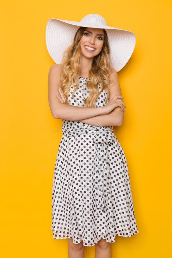 Mujer joven sonriente del verano en el sombrero de Sun con los brazos cruzados imagenes de archivo