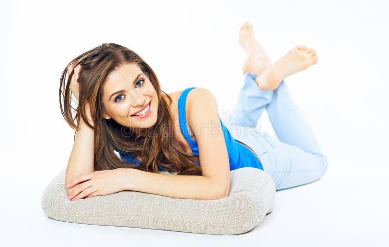 Mujer joven sonriente dentuda que miente en un piso blanco con la almohada foto de archivo