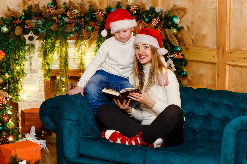 Mujer joven sonriente en calcetines rojos y muchacho que se sienta en el sofá con el libro cerca de la chimenea, de la madre y de imágenes de archivo libres de regalías