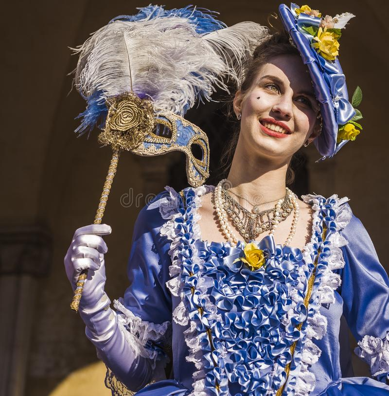 Mujer joven sonriente en el carnaval de Venecia con un traje azul elegante foto de archivo libre de regalías
