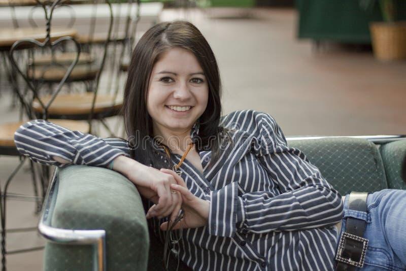 Mujer joven sonriente en el sofá imagen de archivo libre de regalías