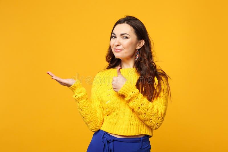 Mujer joven sonriente en el suéter, pantalones azules que miran la cámara, señalando la mano a un lado, mostrando el pulgar encim imagen de archivo