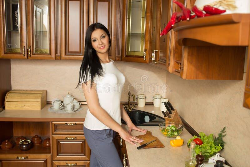Mujer joven sonriente en la cocina con las verduras fotografía de archivo