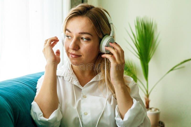 Mujer joven sonriente en los auriculares que se relajan en el sofá y que miran lejos en casa fotos de archivo