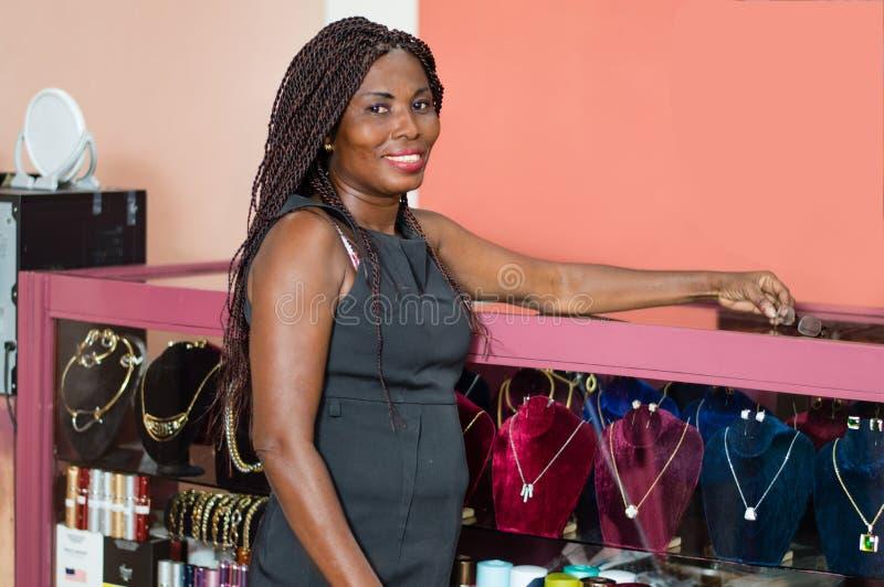 Mujer joven sonriente en su joyería imagen de archivo libre de regalías