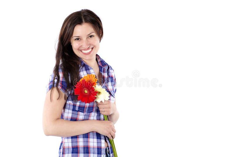 Mujer joven sonriente en una camisa de tela escocesa con el isolat de las flores del gerbera imagen de archivo libre de regalías