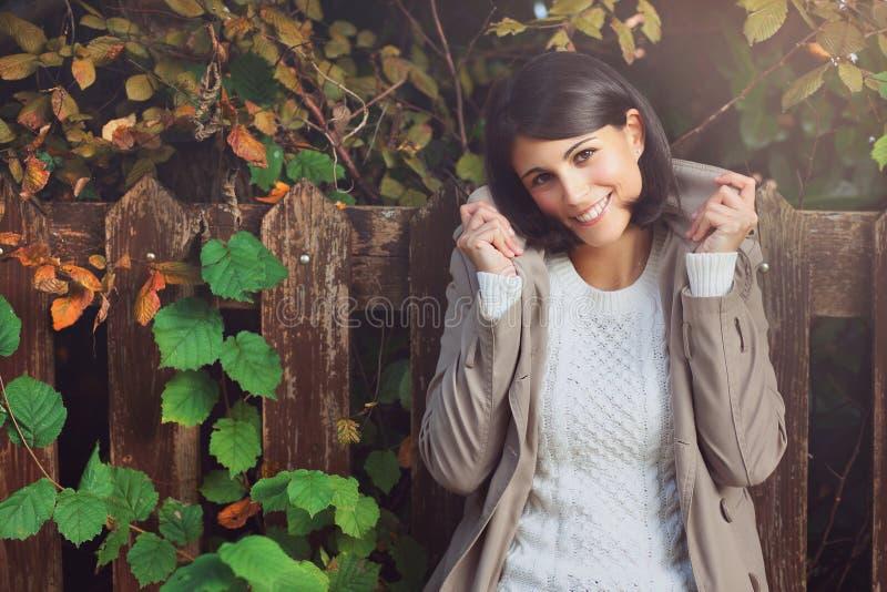 Mujer joven sonriente entre las hojas de otoño imagenes de archivo