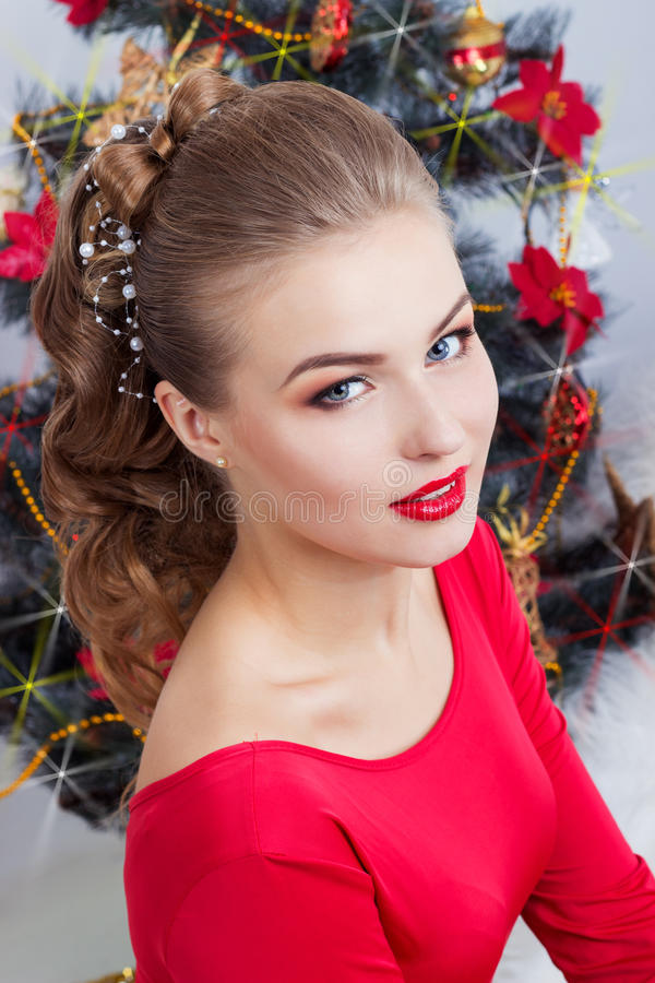 Mujer joven sonriente feliz atractiva hermosa en vestido de noche con maquillaje brillante con el lápiz labial rojo que se sienta imagenes de archivo