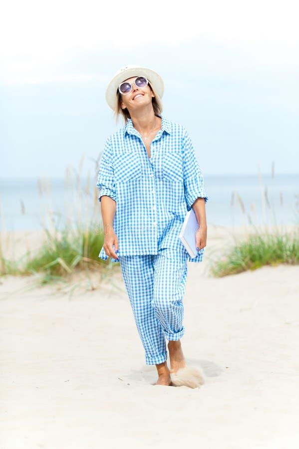 Mujer joven sonriente feliz en el sombrero y las gafas de sol del verano que sostienen el libro que camina en la arena de la play foto de archivo