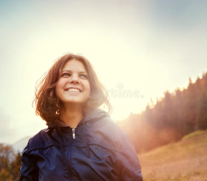 Mujer joven sonriente feliz en luz de la puesta del sol en la colina de la montaña fotografía de archivo