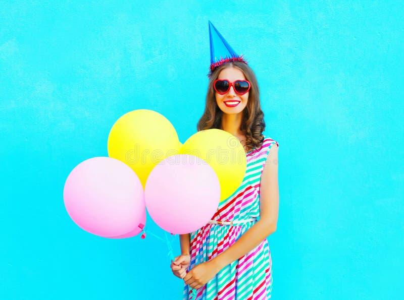 Mujer joven sonriente feliz en un casquillo del cumpleaños con los globos coloridos de un aire sobre un azul fotografía de archivo
