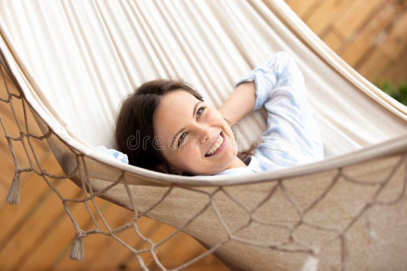 Mujer joven sonriente feliz que miente en la hamaca que mira en distancia imagenes de archivo