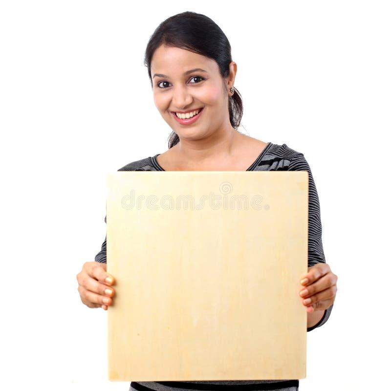 Mujer joven sonriente feliz que sostiene la hoja de madera en blanco fotos de archivo