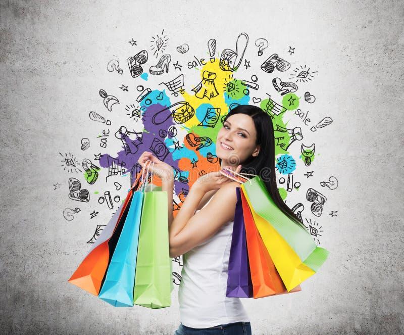 Mujer joven sonriente hermosa con los panieres coloridos de las tiendas de lujo imagen de archivo libre de regalías
