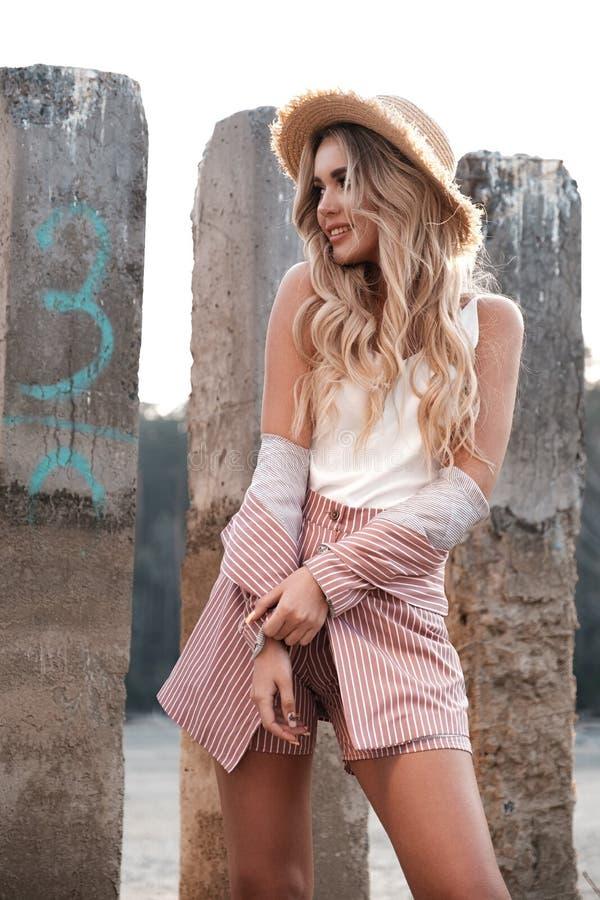 Mujer joven sonriente hermosa, de moda y natural con el pelo rubio flojo largo en un sombrero de paja Paisaje del campo, piedras  fotografía de archivo libre de regalías
