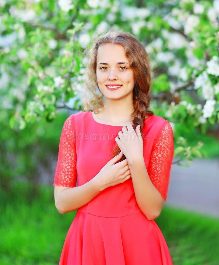 Mujer joven sonriente hermosa en jardín floreciente imagen de archivo