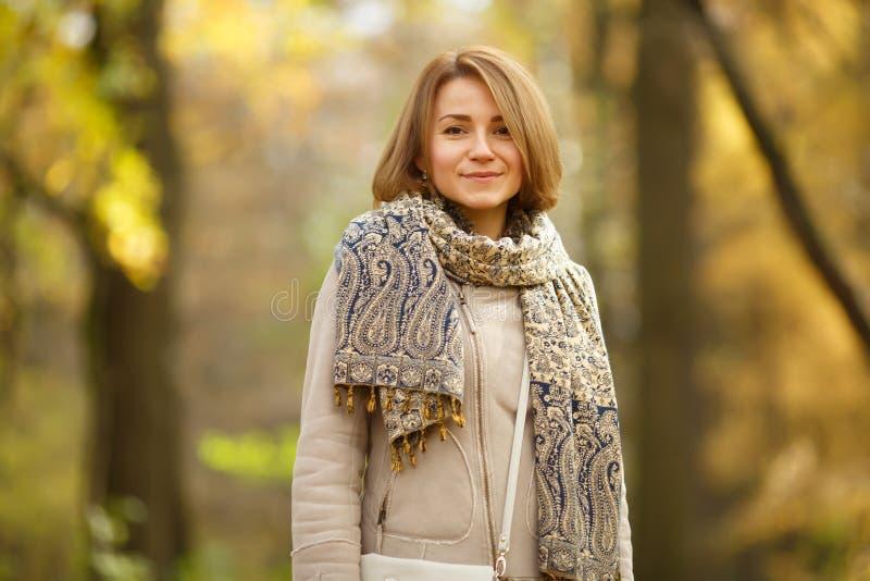 Mujer joven sonriente hermosa en parque del otoño imagen de archivo