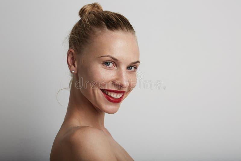 Mujer joven sonriente hermosa Fondo blanco imagen de archivo