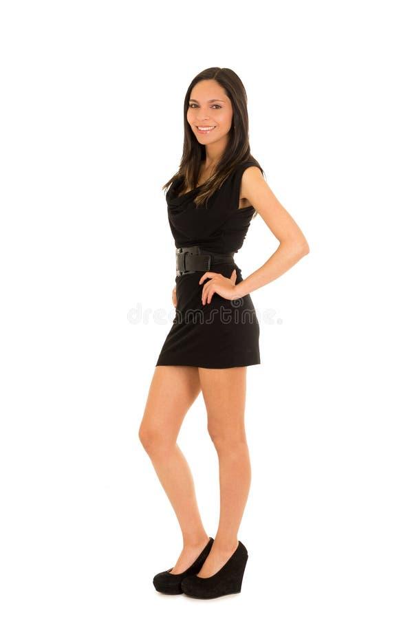 Mujer joven sonriente hermosa, llevando un vestido negro y presentando para la cámara, en un fondo blanco imágenes de archivo libres de regalías