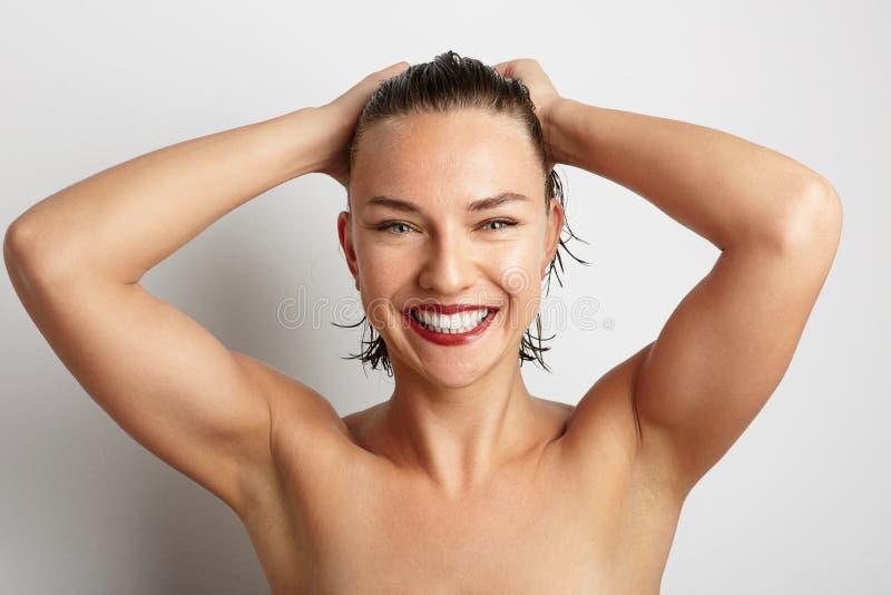 Mujer joven sonriente hermosa Sobre el fondo blanco fotografía de archivo libre de regalías
