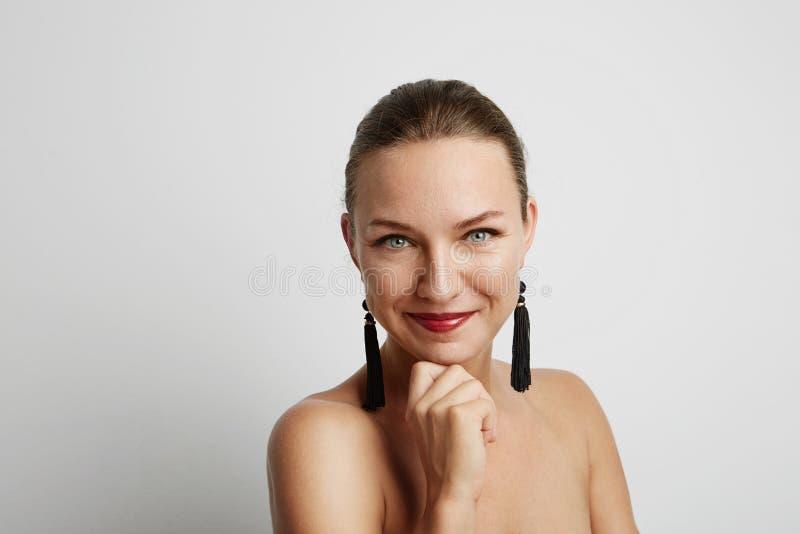 Mujer joven sonriente hermosa Sobre el fondo blanco imagen de archivo