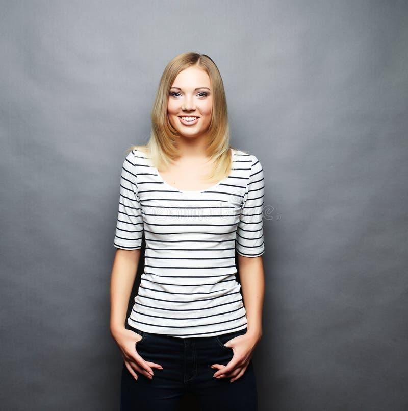 Mujer joven sonriente hermosa Sobre fondo gris foto de archivo libre de regalías