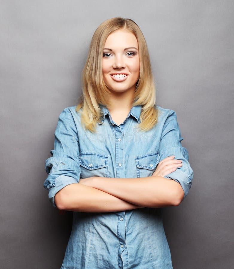 Mujer joven sonriente hermosa Sobre fondo gris fotografía de archivo
